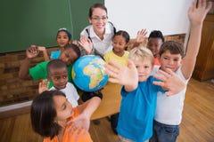 Allievi svegli che sorridono intorno ad un globo in aula con l'insegnante Fotografie Stock Libere da Diritti