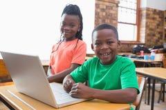 Allievi svegli che utilizzano computer portatile nell'aula Immagini Stock