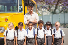 Allievi svegli con il loro driver di scuolabus Fotografia Stock Libera da Diritti