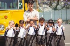 Allievi svegli con il loro driver di scuolabus Immagine Stock