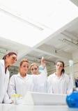 Allievi svegli di chimica che esaminano un fkask Fotografia Stock