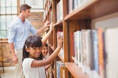 Allievi svegli ed insegnante che cercano i libri in biblioteca Immagine Stock