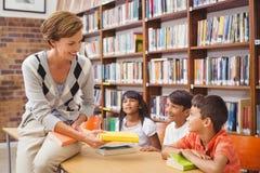Allievi svegli ed insegnante che cercano i libri in biblioteca Immagini Stock