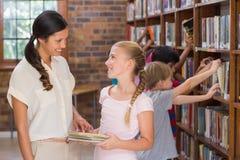 Allievi svegli ed insegnante che cercano i libri in biblioteca Fotografia Stock
