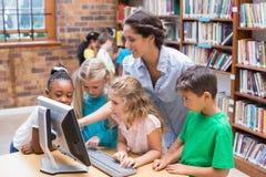 Allievi svegli ed insegnante che esaminano computer in biblioteca Immagine Stock