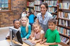 Allievi svegli ed insegnante che esaminano computer in biblioteca Fotografia Stock Libera da Diritti