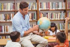 Allievi svegli ed insegnante che esaminano globo in biblioteca Immagine Stock