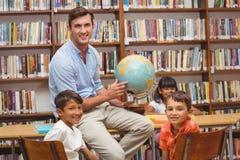 Allievi svegli ed insegnante che esaminano globo in biblioteca Immagini Stock Libere da Diritti