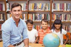 Allievi svegli ed insegnante che esaminano globo in biblioteca Fotografie Stock Libere da Diritti