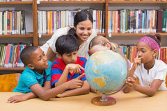 Allievi svegli ed insegnante che esaminano globo in biblioteca Fotografia Stock