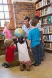 Allievi svegli ed insegnante che esaminano globo in biblioteca Fotografie Stock