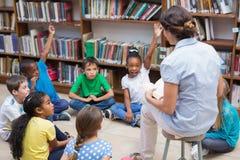 Allievi svegli ed insegnante che hanno classe in biblioteca Immagine Stock Libera da Diritti