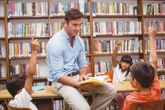 Allievi svegli ed insegnante che hanno classe in biblioteca Fotografia Stock Libera da Diritti
