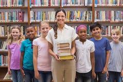 Allievi svegli ed insegnante che hanno classe in biblioteca Fotografia Stock