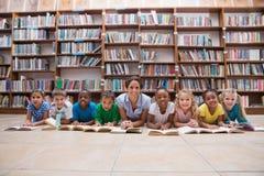 Allievi svegli ed insegnante che si trovano sul pavimento in biblioteca Fotografia Stock Libera da Diritti