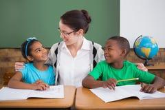 Allievi svegli ed insegnante che sorridono ad a vicenda in aula Immagine Stock