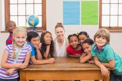 Allievi svegli ed insegnante che sorridono alla macchina fotografica in aula Fotografia Stock