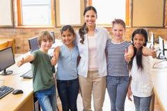 Allievi svegli ed insegnante che sorridono alla macchina fotografica nella classe del computer Fotografie Stock Libere da Diritti