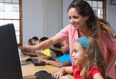 Allievi svegli nella classe del computer con l'insegnante Immagine Stock