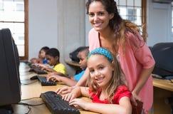 Allievi svegli nella classe del computer con l'insegnante Immagini Stock