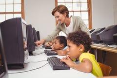 Allievi svegli nella classe del computer con l'insegnante Fotografie Stock Libere da Diritti