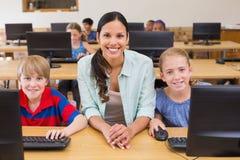 Allievi svegli nella classe del computer con l'insegnante Fotografia Stock