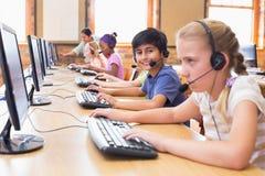 Allievi svegli nella classe del computer con l'insegnante Immagine Stock Libera da Diritti