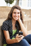 Allievo adolescente che si siede fuori del per mezzo del telefono mobile Immagine Stock