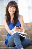 Allievo adolescente che si siede sui punti dell'istituto universitario Fotografia Stock Libera da Diritti