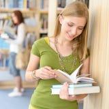 Allievo adolescente con il libro alla libreria della High School Immagini Stock Libere da Diritti
