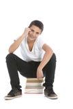 Allievo adolescente felice che si siede sui suoi libri Fotografie Stock Libere da Diritti