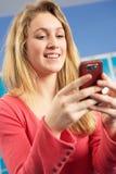 Allievo adolescente femminile che per mezzo del telefono mobile Immagine Stock