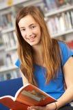 Allievo adolescente femminile in libro di lettura delle biblioteche Fotografia Stock