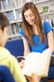 Allievo adolescente femminile in libro di lettura delle biblioteche Fotografie Stock