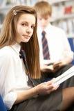 Allievo adolescente femminile in libro di lettura delle biblioteche Immagine Stock