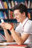 Allievo adolescente maschio che manda un sms nell'aula Fotografia Stock Libera da Diritti