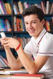 Allievo adolescente maschio che manda un sms nell'aula Immagini Stock Libere da Diritti