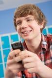 Allievo adolescente maschio che per mezzo del telefono mobile Fotografia Stock