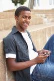 Allievo adolescente maschio che si siede all'esterno Immagine Stock