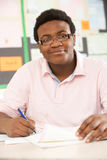 Allievo adolescente maschio che studia nell'aula Fotografie Stock