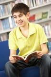 Allievo adolescente maschio in libro di lettura delle biblioteche Fotografie Stock Libere da Diritti