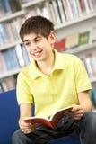 Allievo adolescente maschio in libro di lettura delle biblioteche Immagine Stock