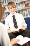 Allievo adolescente maschio in libro di lettura delle biblioteche Fotografia Stock