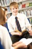Allievo adolescente maschio in libro di lettura delle biblioteche Immagini Stock