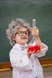 Allievo agghindato che esamina liquido rosso Fotografia Stock Libera da Diritti