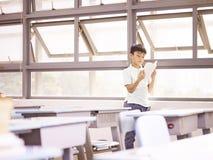 Allievo asiatico che legge un libro dalle finestre Fotografia Stock