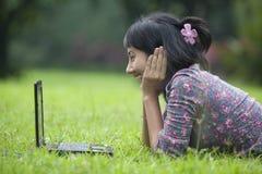 Allievo asiatico che per mezzo del computer portatile esterno Fotografie Stock