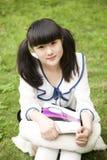 Allievo asiatico nella lettura della città universitaria Fotografia Stock