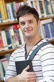 Allievo astuto che tiene un libro che si leva in piedi in una libreria Fotografia Stock Libera da Diritti