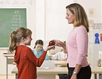 Allievo che dà la mela dell'insegnante Fotografia Stock
